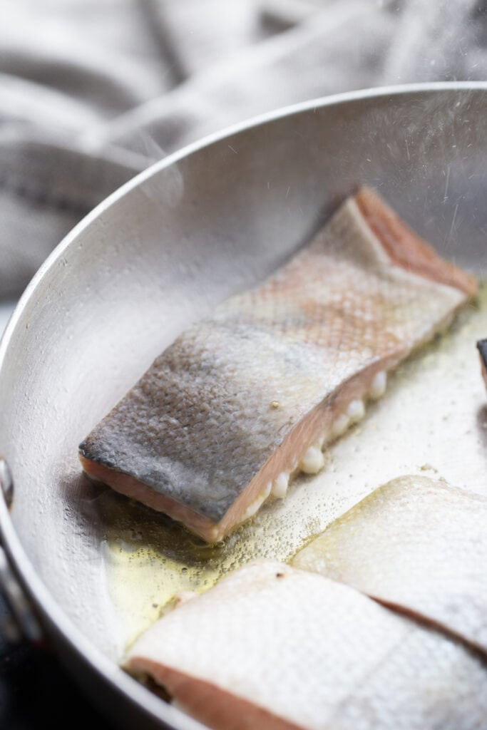 Salmon cooking skin side up in a stainless steel pan.