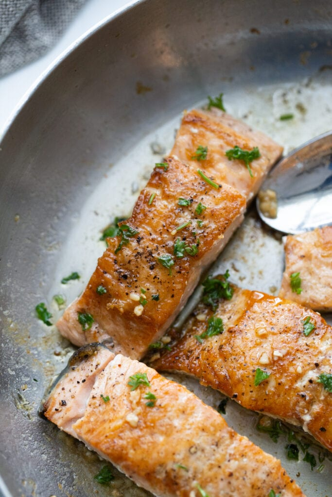 Crispy salmon finished with butter and garlic sauce in a stainless pan