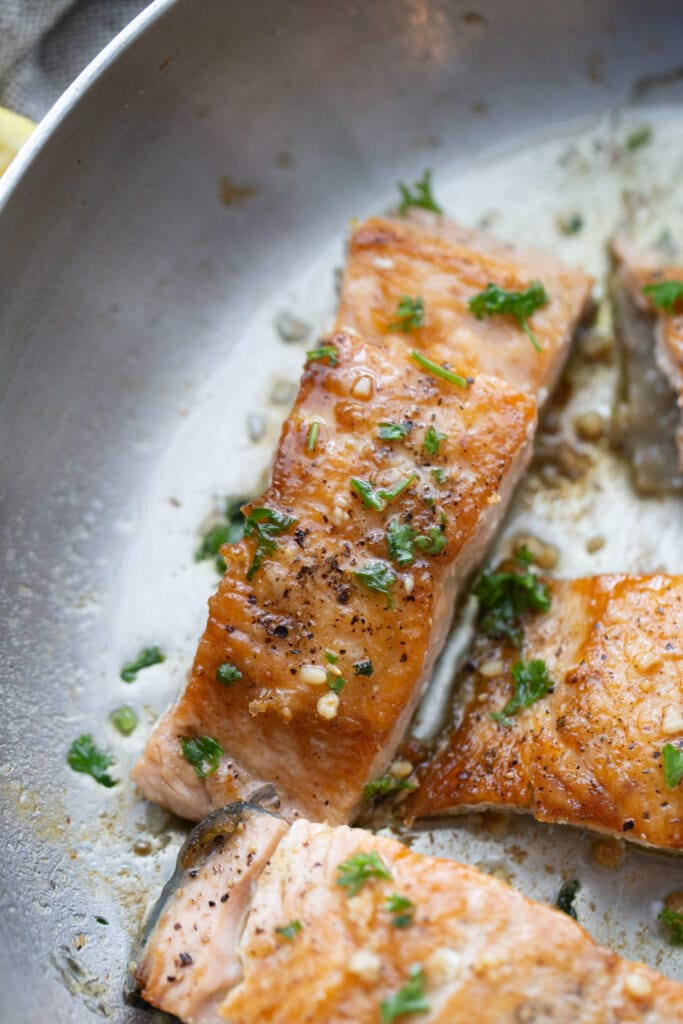 Crispy salmon fillets in a stainless steel pan