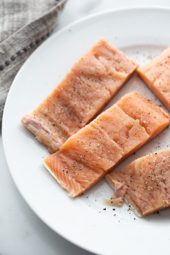 Raw salmon fillets seasoned with salt and pepper.