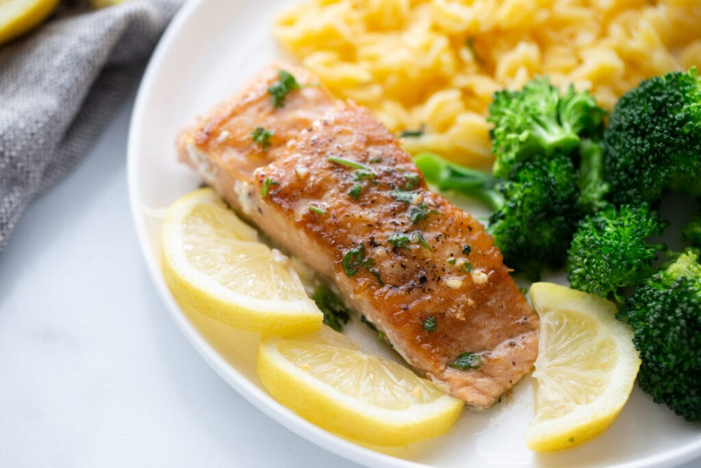 Pan seared salmon on a white plate with sliced lemons and sides of broccoli and gluten free orzo.