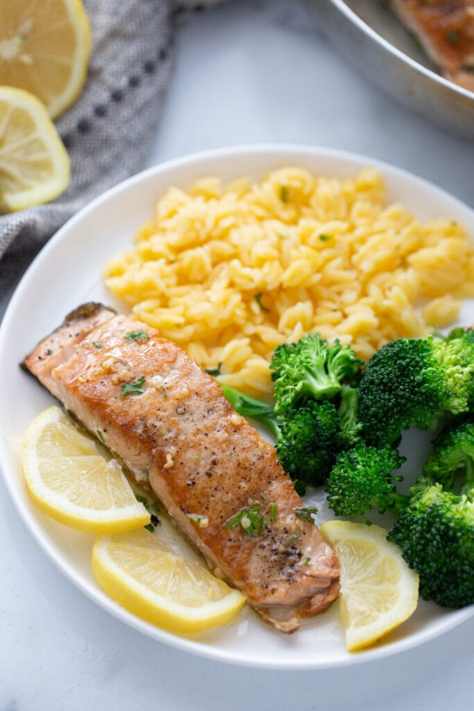 High angle photo of a crispy salmon fillet on a white plate with broccoli and gluten free orzo.