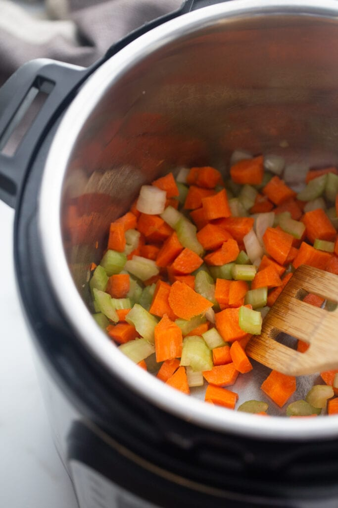 Carrots, onions and celery are sautéed in the Instant Pot.