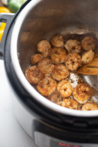 Cooked shrimp are being stirred with a wooden spoon in the Instant Pot.