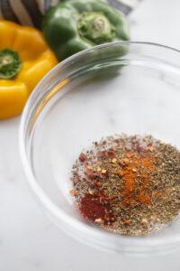 A glass bowl contains the seasonings for homemade cajun seasoning.