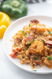 A white plate presents a perfect portion of healthy jambalaya.