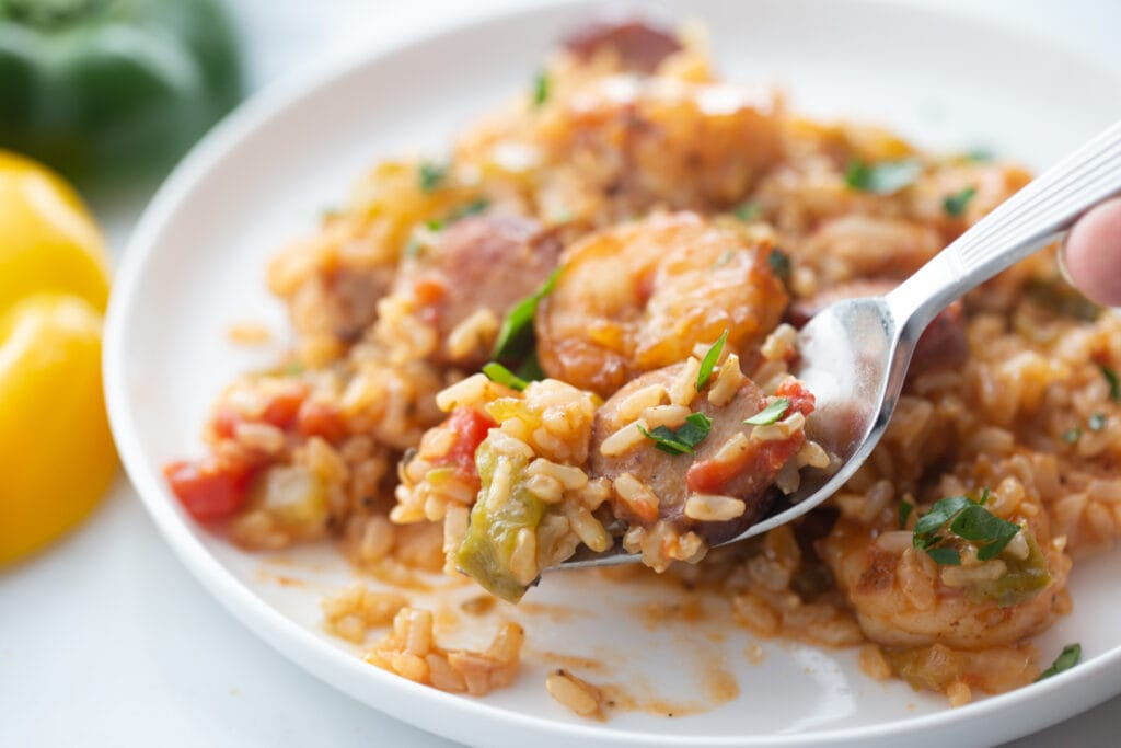 A spoon is picking up a small bite of jambalaya from a white plate.