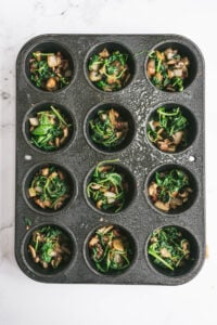 Freshly cooked veggies are placed on top of bacon bits in muffin tins.