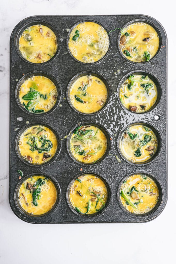Whisked eggs have been poured on top of the veggies and bacon in the muffin tins.