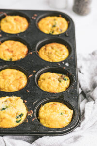 Eight perfectly baked egg bites are in muffin tins.