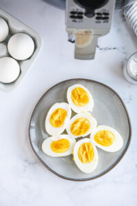 A plate of hard boiled eggs is placed next to raw eggs and an air fryer.
