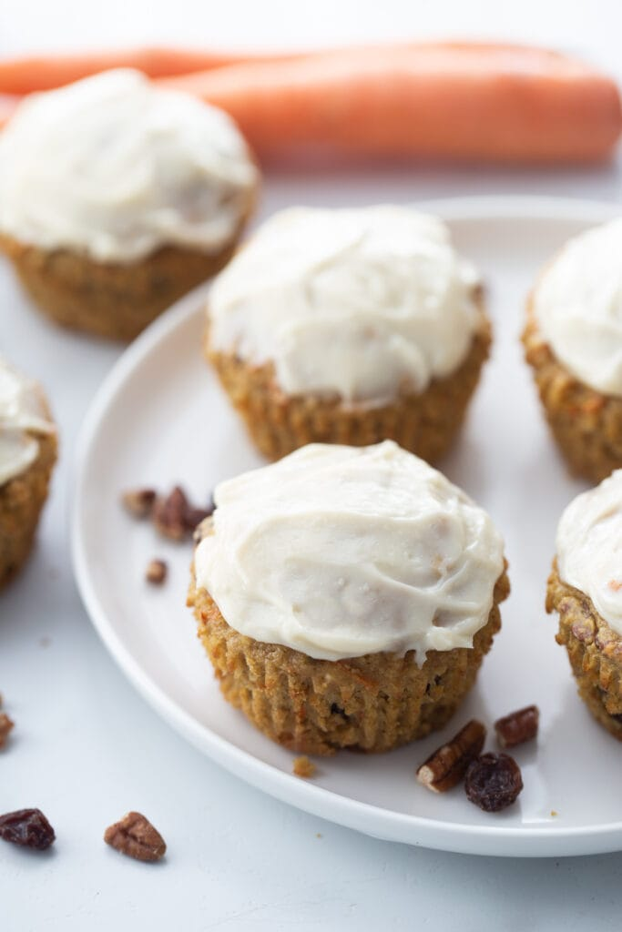 Six carrot cake muffins with frosting on a white plate