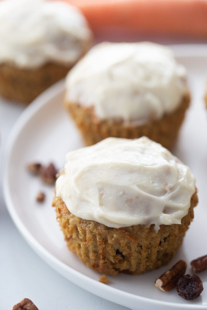 Two carrot cake muffins topped with cream cheese frosting on a white plate