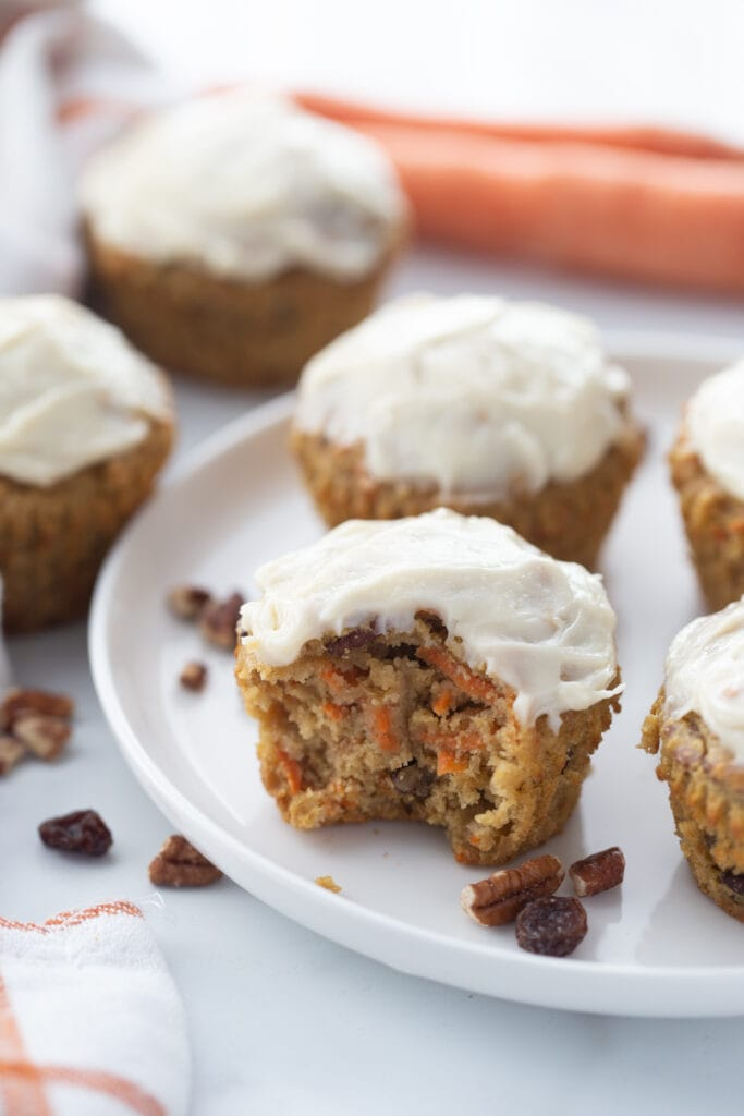 Carrot Cake muffins topped with cream cheese frosting on a white plate. Some cakes are in the background off of the serving plate.