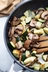Fresh vegetables are being cooked in a skillet.
