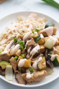 Rice and hibachi chicken are drizzled with yum yum sauce on a plate.