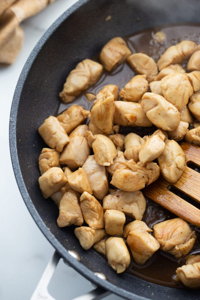 Browned chicken is being stirred by a wooden spoon in a black skillet.
