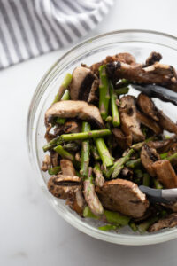 Asparagus and mushrooms are mixed in a glass bowl.