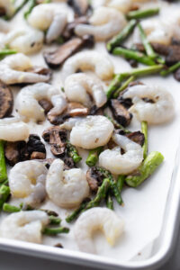 Shrimp and veggies are spread out on a baking sheet.