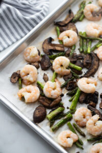 Baked shrimp and veggies are on a baking sheet.
