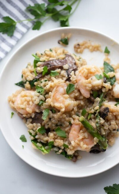 A white plate contains a serving of shrimp risotto.