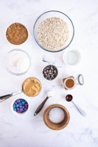 The ingredients for monster cookies are presented on a white surface.