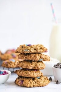A stack of monster cookies is presented on a white surface.