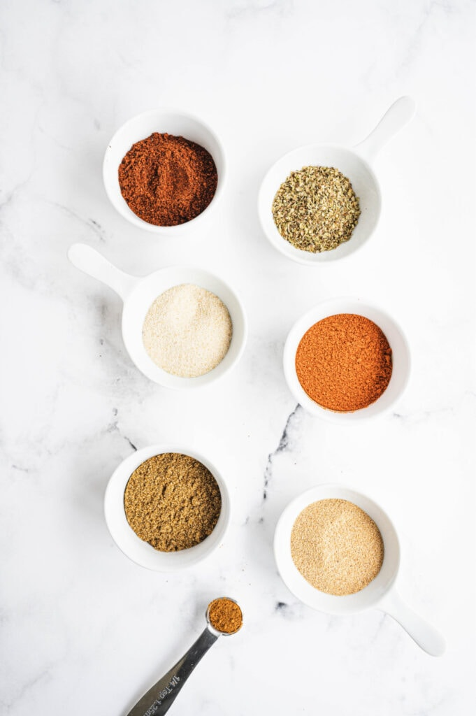 Overhead photo of small white bowls and a measuring spoon, full of spices for homemade taco seasoning