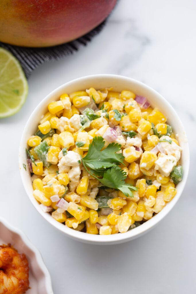 A bowl of Mexican Street corn salad on a white background