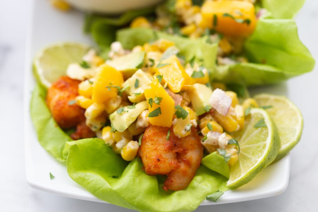 A close up photo of air fryer shrimp tacos, mango, street corn salad, and avocado with lime wedges as a garnish