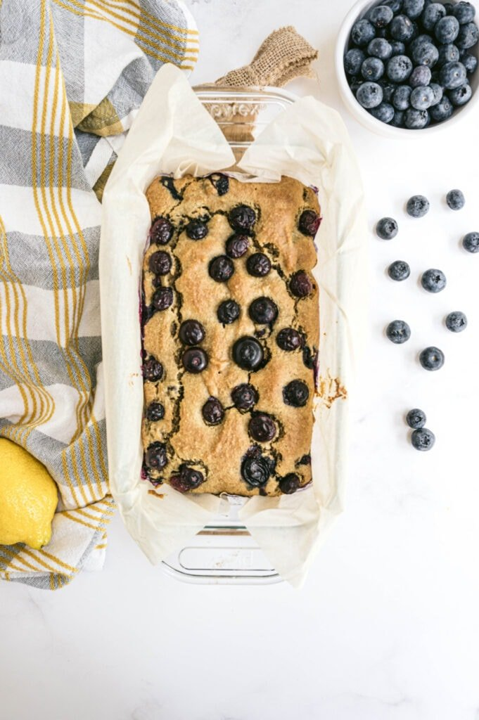 Overhead image of lemon blueberry loaf topped with blueberries and sitting on a white background