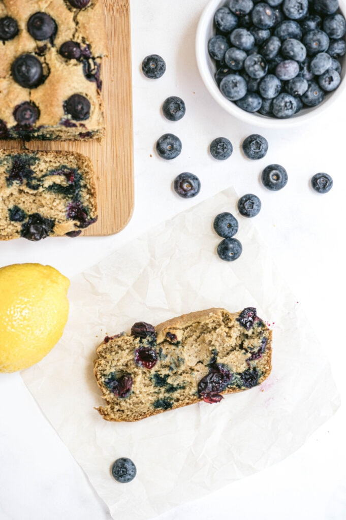 Healthy lemon blueberry bread with lemon and a bowl of blueberries sitting nearby. A piece of blueberry bread is sitting on parchment.