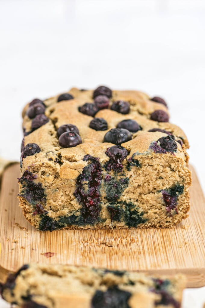 Closeup of lemon blueberry loaf on a cutting board with one slice removed from the bread