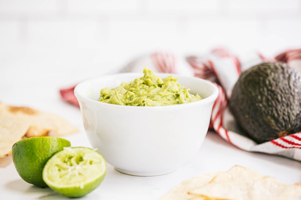 A white bowl of homemade guacamole with a chips, some fresh lime and avocado the background