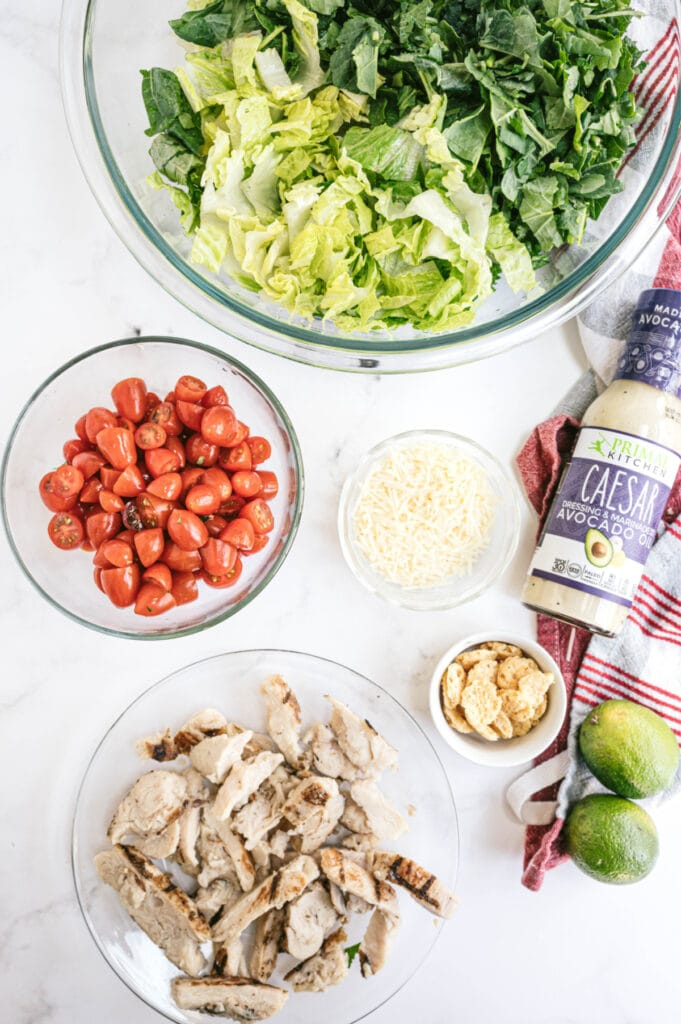Overhead photo of ingredients in glass bowls - Greens, chopped tomatoes, diced grilled chicken, Parmesan, and Caesar dressing