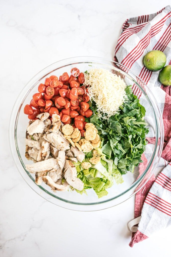 Overhead image: bowl of kale Caesar chicken salad, separated by ingredient