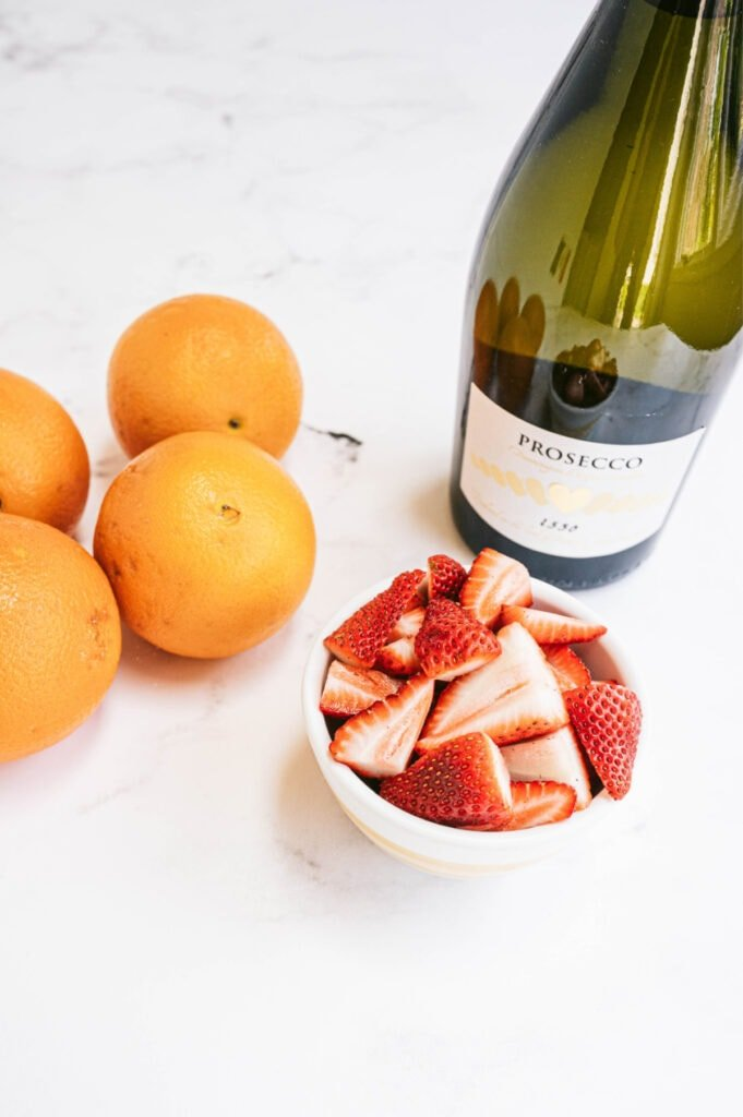 A small bowl of strawberries, some oranges, and a bottle of prosecco on a white counter