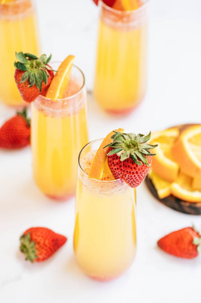 Champagne flutes with orange strawberry mimosas on a white table and a strawberry garnish