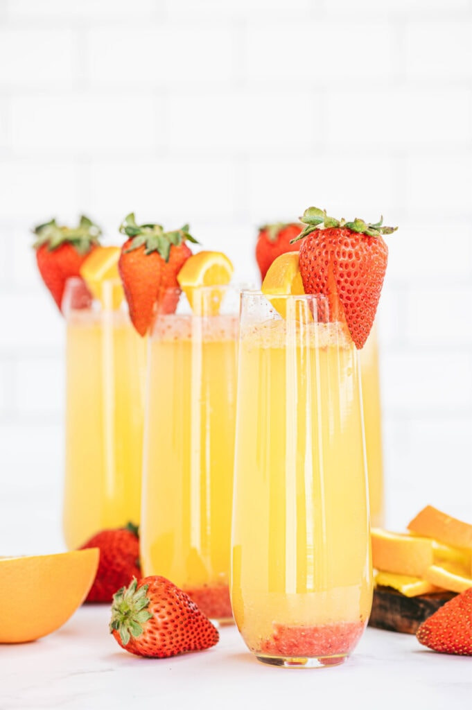 Champagne flutes with orange strawberry mimosas and a strawberry garnish
