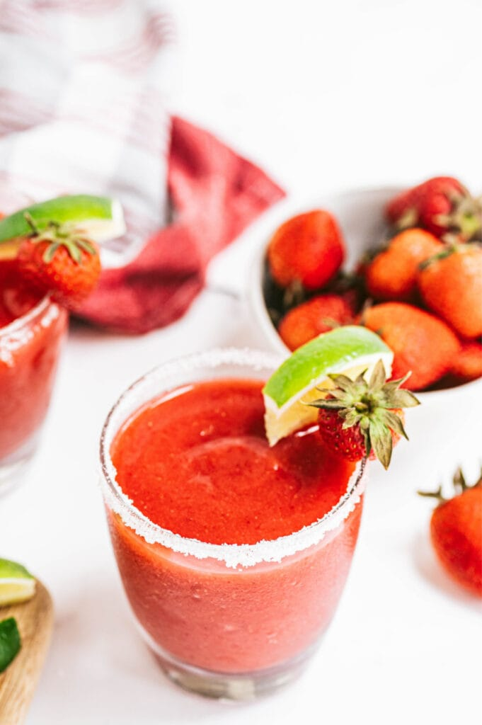 An overhead shot of a salt rimmed glass filled with Frozen Strawberry Rhubarb Margarita garnished with lime and strawberries