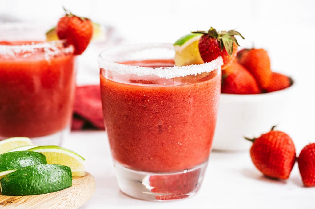 Strawberry Rhubarb Margarita garnished with lime and strawberries and a bowl of berries and some lime in the background