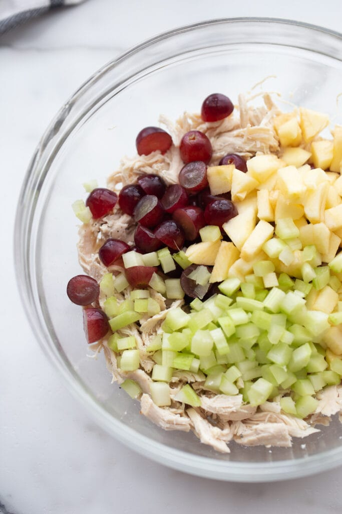 A bowl of chicken salad mix-ins - apples, grapes, celery, and chicken