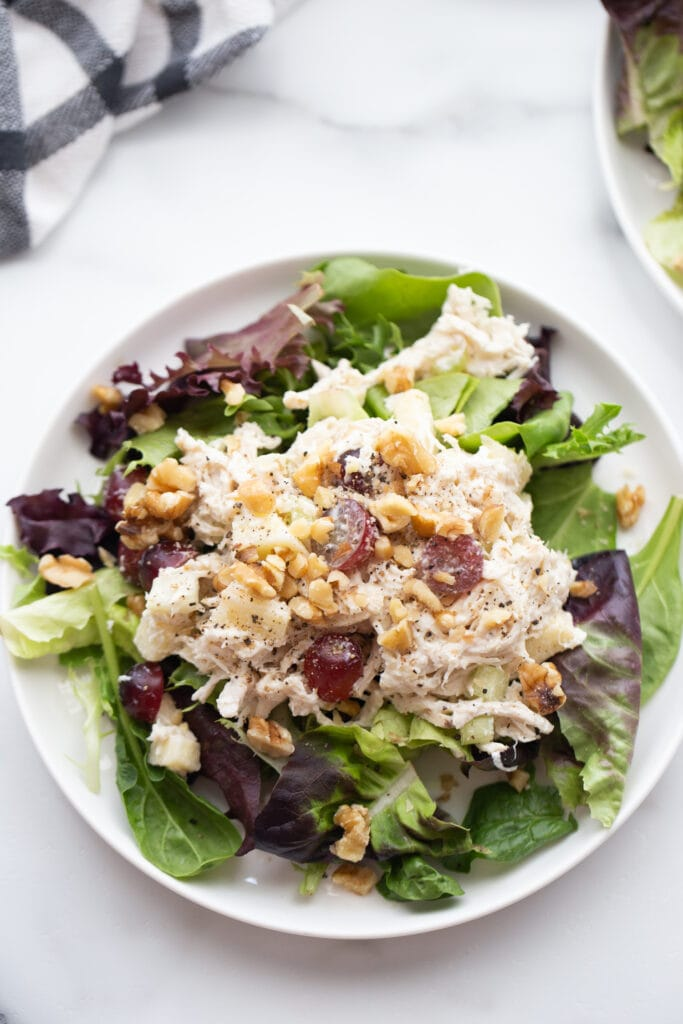 Overhead shot of a healthy chicken salad recipe on mixed greens