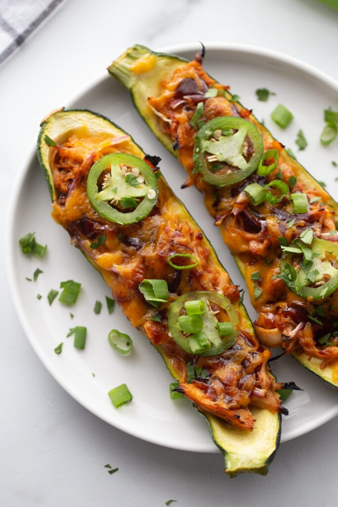 Overhead image: zucchini sliced lengthwise and stuffed with BBQ chicken and topped with cheese, all cooked and on a white plate