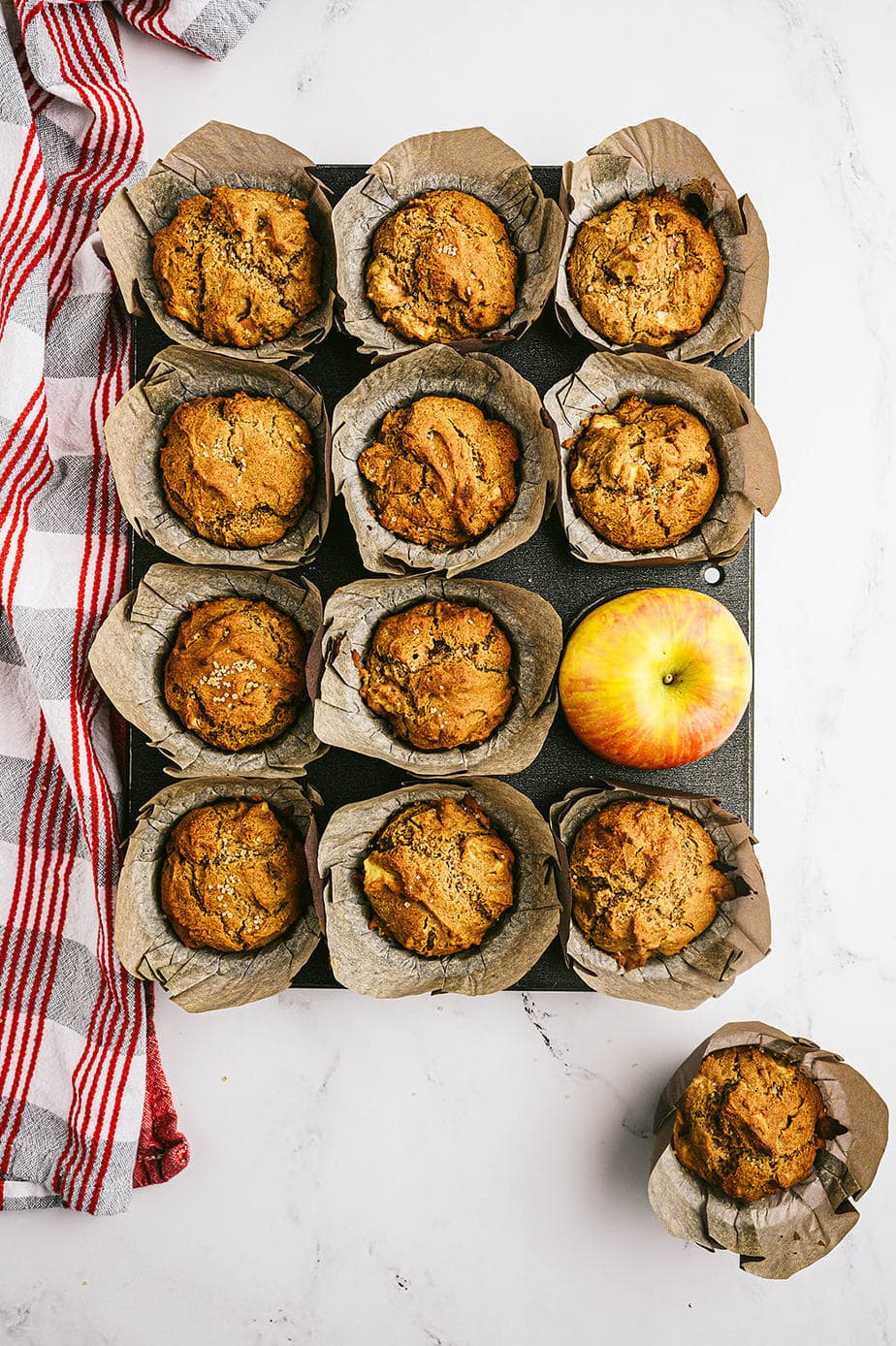 Overhead photo: muffin tin full of cooked muffins with a whole apple taking one's place.