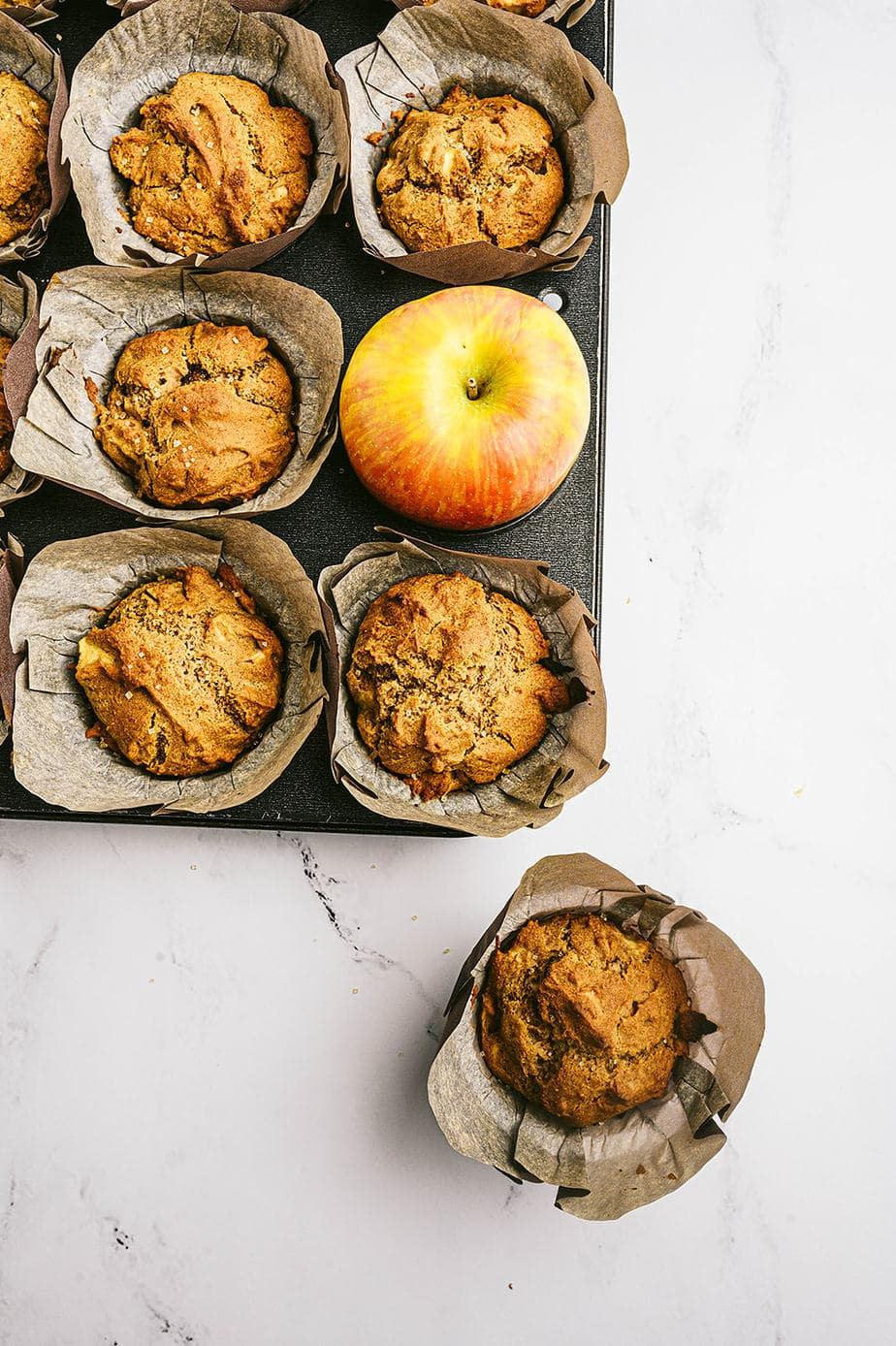 Overhead image: parchment lined muffins in a muffin tin. One muffin is out of its place, off to the side and a whole apple takes its place in the tin.