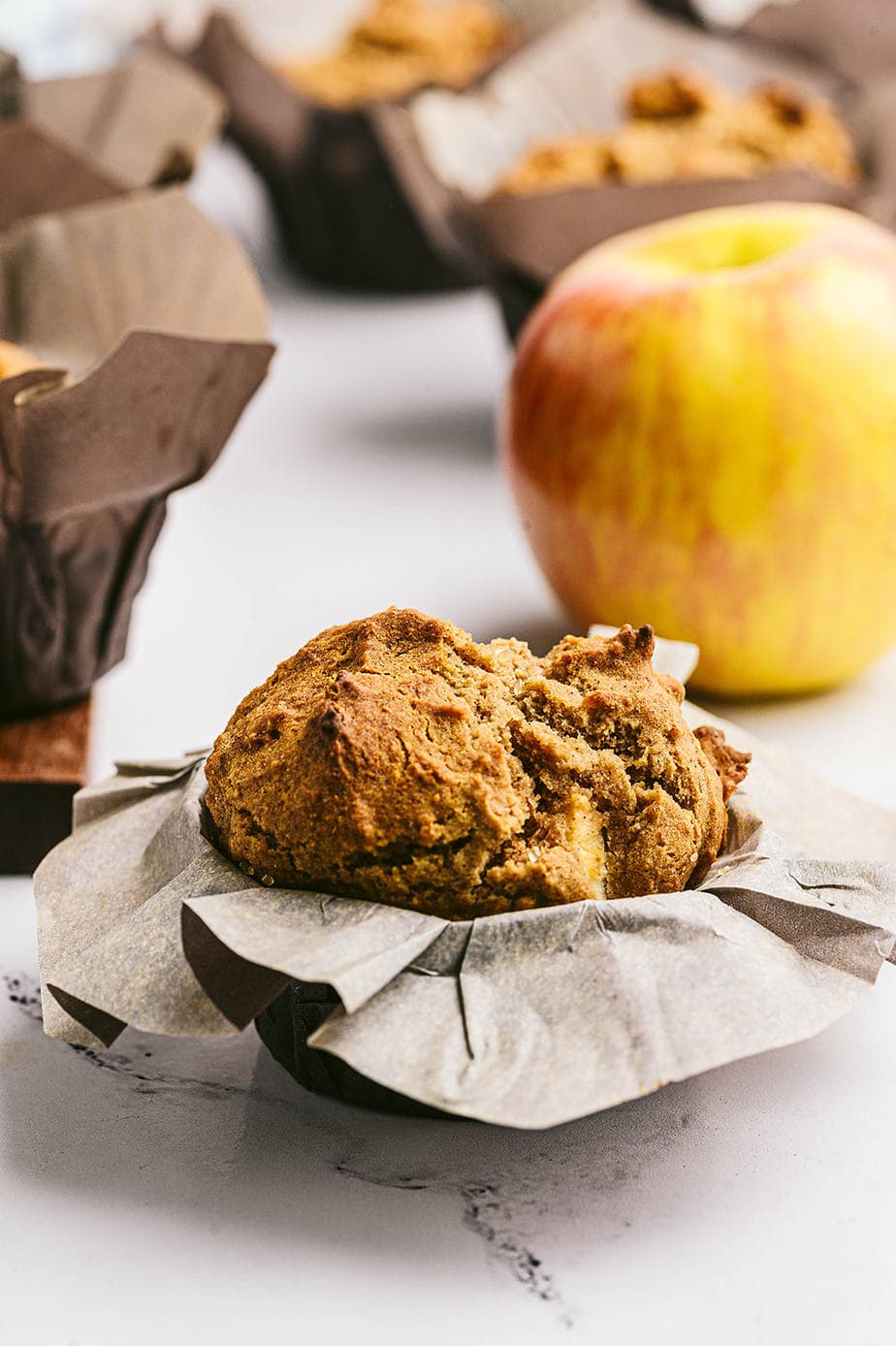 Side view: Healthy apple muffin wrapped in parchment, with many muffins in the background