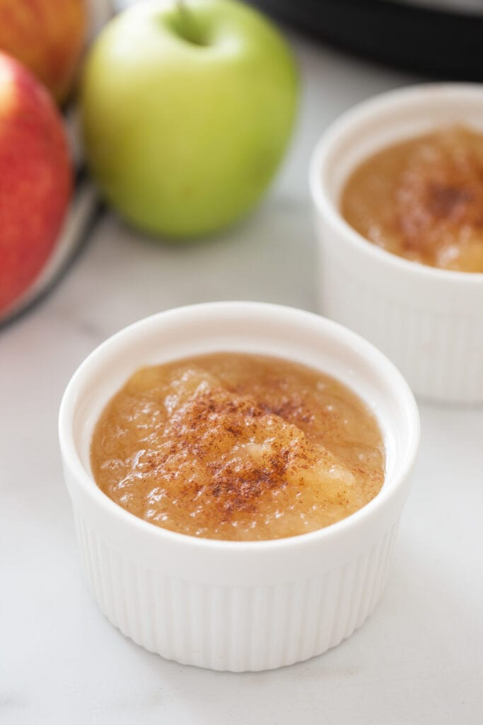 Two ramekins of homemade instant pot applesauce with cinnamon sprinkled on top