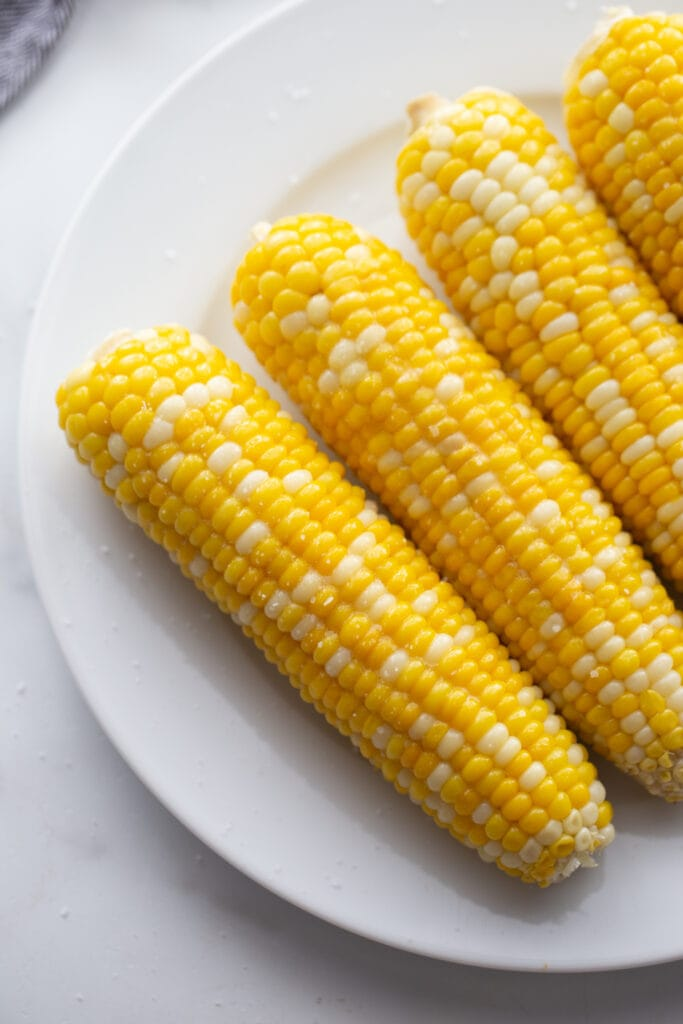 Overhead image: corn on the cob lined up on a white plate