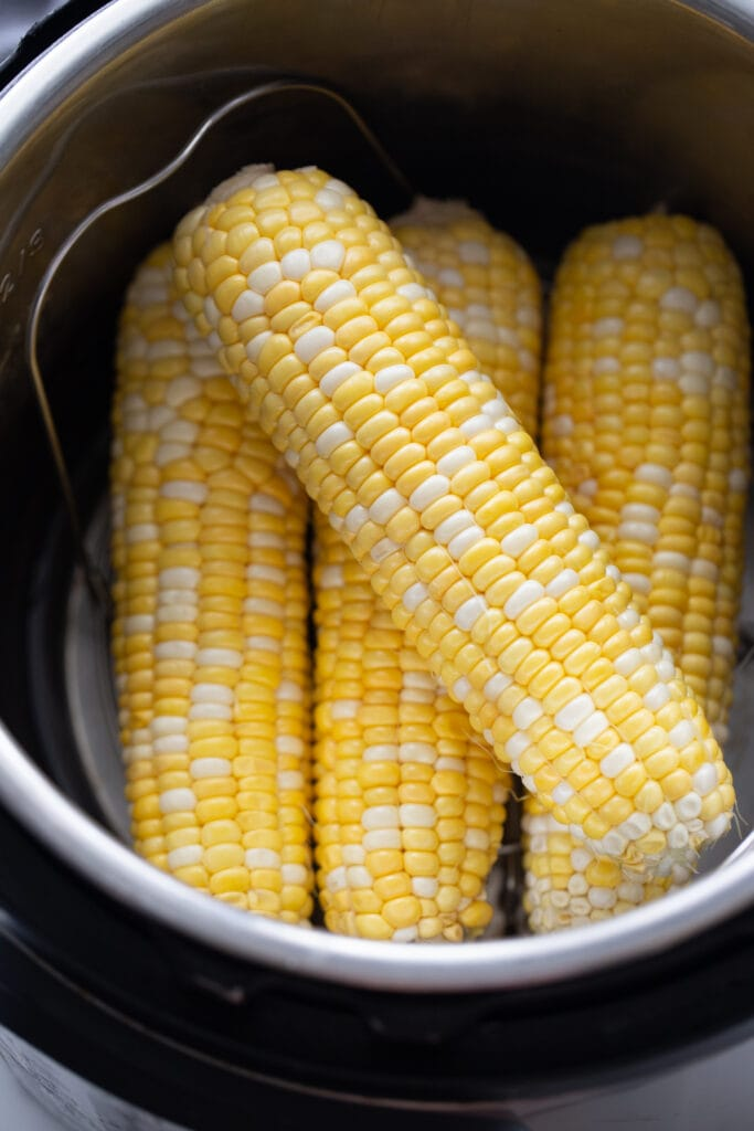 Overhead image: Corn on the cob in the instant pot, ready to be cooked